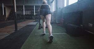 Willpower and motivation, camera follows young athletic woman pushing heavy training sled training in gym slow motion. Professional blonde female athlete doing stock video