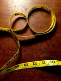 Willpower. Vertical view of yellow measuring tape on antique wood table. Space for text Royalty Free Stock Photography