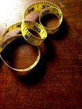 Willpower. Vertical view of yellow measuring tape on antique wood table. Space for text Royalty Free Stock Images