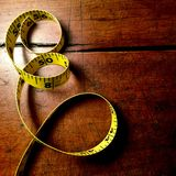 Willpower. Yellow measuring tape on antique wood table. Space for text Royalty Free Stock Images