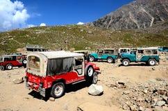 Willys jeepar som parkeras på bergssidadalen i Pakistan Arkivfoto