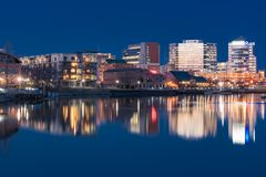 Wilmington, Delaware Skyline Along Riverwalk. WILMINGTON, DE - APRIL 5, 2018: Wilmington, Delaware night skyline and Riverwalk along the Christiana River stock photo