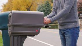 Wilson, Nueva York - octubre de 2016: Reparto del correo de los E.E.U.U. El hombre anónimo coge el correo del buzón al lado del c almacen de metraje de vídeo