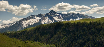 Wilson Peak, Telluride, Colorado, with Summer Snow. Under radiant clouds, the Rocky Mountains iconic Wilson Peak sits int he afternoon sun, still wearing snow Royalty Free Stock Image
