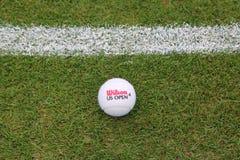 Wilson US Open Tennis Ball on grass tennis court. NEW YORK - JULY 21, 2015:  Wilson US Open Tennis Ball on grass tennis court. Wilson is the Official Ball of the Stock Photos