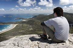 Wilsons Prom. Young man sitting high on hill overloooking blue sky and beach royalty free stock photography