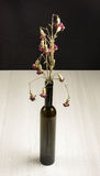 Wilted carnation flowers on the grey wooden table. Wilted flowers in the black glass bottle Stock Images