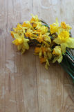 Wilted daffodil flowers on a wooden table. Vertical aspect Royalty Free Stock Image