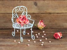 Wilted roses on armchair and pearls on wooden background. royalty free stock photos