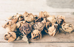 Wilted roses on wooden table Royalty Free Stock Images