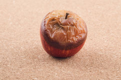Wilted rotten apple on brown background. Wilted rotten apple on brown background Royalty Free Stock Photos