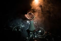 A wilting rose signifies lost love, divorce, or a bad relationship, dead rose on dark background with smoke. Selective focus royalty free stock image