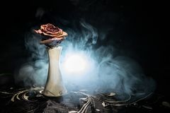A wilting rose signifies lost love, divorce, or a bad relationship, dead rose on dark background with smoke. Selective focus stock photo