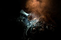 A wilting rose signifies lost love, divorce, or a bad relationship, dead rose on dark background with smoke. Selective focus royalty free stock photo