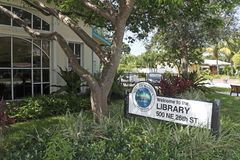Wilton Manors Island City Library Sign. Wilton Manors, FL, USA - August 25, 2017: Building front and Welcome to the Library sign at 500 NE 26th St. Summer day stock photography