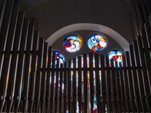 A stained glass rose window behind the organ pipes of the pipe organ in the Church of Wilwerdange, Luxembourg stock image