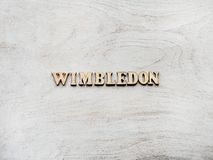 WIMBLEDON. Beautiful, bright photo for invitation card. WIMBLEDON. Wooden, unpainted letters on a white table. Close-up, top view. Beautiful photo for invitation stock photo