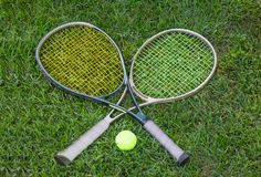 Wimbledon sign, two tennis rackets with a ball. On grass stock photo