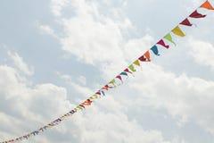 Wimpel-Schnur mit weißen Wolken im blauen Himmel stockfotografie