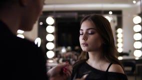 Wimpers van make-up maken de hoofdverhogingen, omhoog kunstenaar die lange zwepen maken, maakt de vrouw in schoonheidsstudio avon stock footage