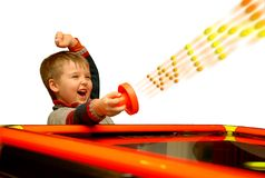 Win !. A child who has won his air hockey game, isolated over a white background. Text WIN consisted of colourful balls in motion Royalty Free Stock Photography