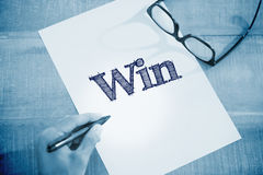 Win against left hand writing on white page on working desk Stock Photography
