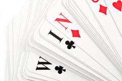 Win concept. Close up on a deck of spread playing cards revealing the word 'WIN' over white Stock Image