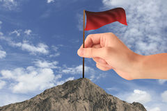 Win concept. Hand placing waving red flag on mountain top. Sky background. Win concept Stock Images