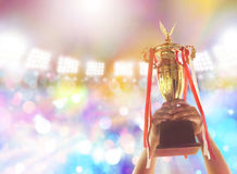 Man holding up a gold trophy cup,win concept. Win concept,Man holding up a gold trophy cup is winner in a competition in night stadium royalty free stock photo
