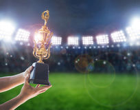 Man holding up a a gold trophy cup,win concept. Win concept,Man holding up a a gold trophy cup is winner in a competition in night stadium stock image