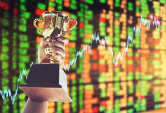 Man holding up a gold trophy cup,win concept. Win concept,Man holding up a gold trophy cup is winner in a competition with stock exchange background stock image