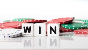Win Concept. Win spelled in dice letters reflected on white isolated background with red, green and white poker chips in the background Stock Image