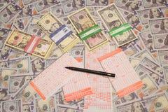 Win de loterij Loterijkaartje en potlood op dollarachtergrond stock afbeelding