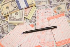 Win de loterij Loterijkaartje en potlood op dollarachtergrond stock foto's