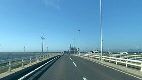 Crossing the bridge to wind turbine and solar farm. Renewable energy. Sunny day with blue sky.