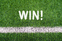 WIN hand writing text on soccer field grass Stock Images