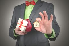 Win a house. Real estate agent is showing a small house in a hand on open gift box background. Win a home in a lottery concept. Special offer to buy a house royalty free stock photos