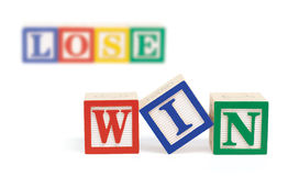 Win Lose Alphabet Blocks. Wooden alphabet blocks on white spelling, win in front row. Further back and out of focus, are blocks spelling the word,  lose Stock Images