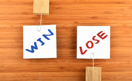 Win lose two paper notes in different directions on wood Royalty Free Stock Photo