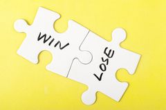 Win and lose words. Written on two pieces of jigsaw puzzle Stock Image