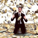 Win money. Businessman exults under a rain of money stock image