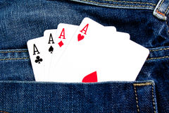 Win with poker game. Details of four poker cards in back pocket jeans stock photo