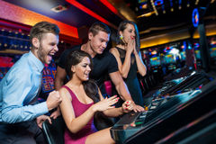Win on slot machine. Group of young people in the hall of slot machines royalty free stock photos