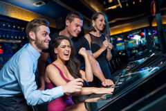 Win on slot machine. Group of young people in the hall of slot machines stock images