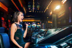 Win on slot machine. Young beautiful girl won on the slot machine Stock Image
