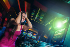 Win on slot machine. Young beautiful girl won on the slot machine Royalty Free Stock Image