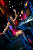 Win on slot machine. Young beautiful girl won on the slot machine Royalty Free Stock Photography