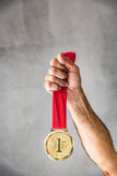 Win and success concept. Senior man holding medal in hand. Win and success concept Stock Photo