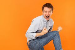 Win! Successful young adult man have a happiness look. Big eyes. And open mouth and looking at camera. Studio shot, orange background stock photo