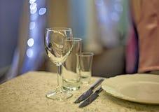 Win szkła, dwa stołowego noża i talerz na stole w r, zdjęcie stock